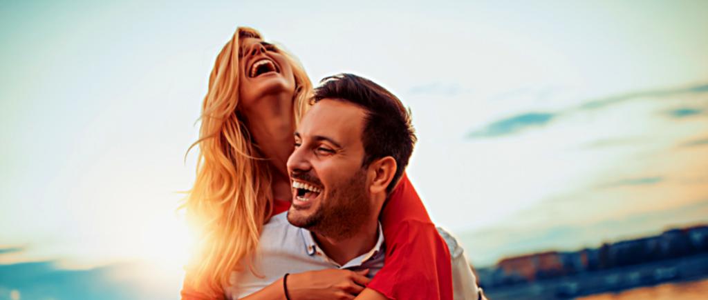 Femme qui rigole sur accroché sur le dos de son mari, couché de soleil en fond