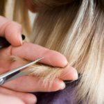 Coiffeur En Train De Couper Des Cheveux Blonds Ciseaux Et Peigne Noir En Main